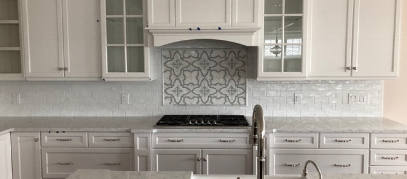 White subway tile with Marble design behind stove. Quartz countertop.