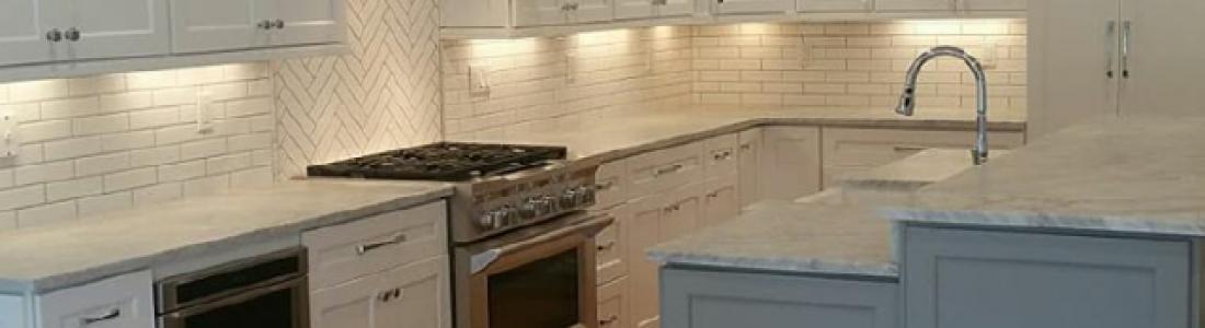 Carrara Honed countertops with 2×8 white subway Backsplash Tile