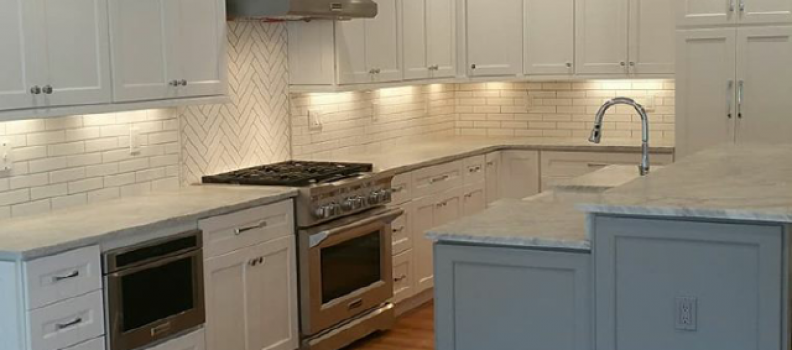 Carrara Honed countertops with 2×8 white subway Backsplash Tile